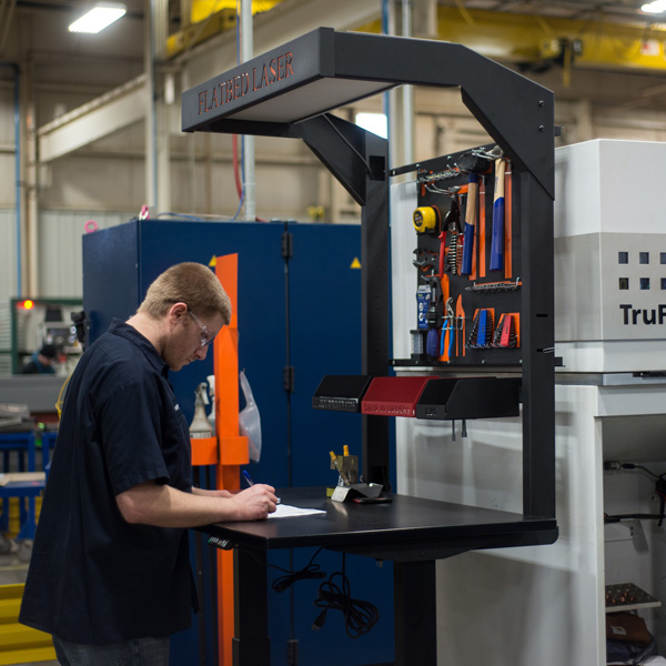 man working at an ergonomic sit stand workbench on manufacturing shop floor next to cnc machine