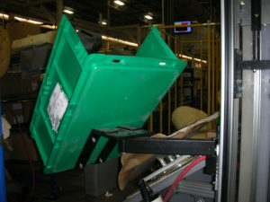 Kaizen Arm mounted to extruded aluminum structure and ergonomically positioning tote bin in industrial warehouse